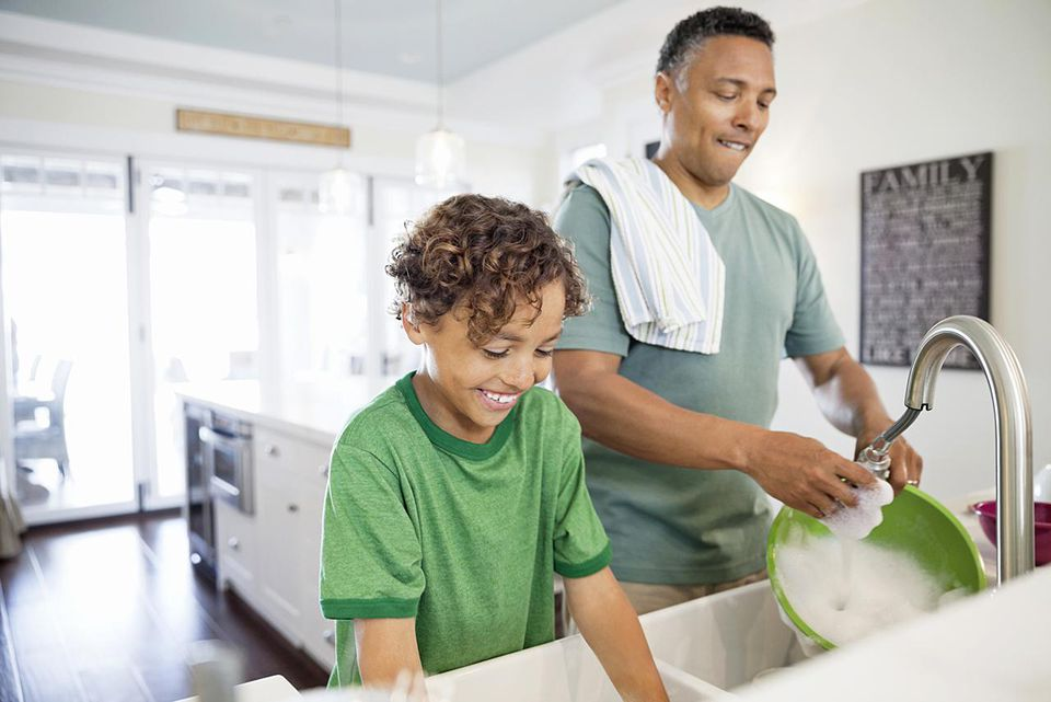 Mature father and son washing dishes together at kitchen sink