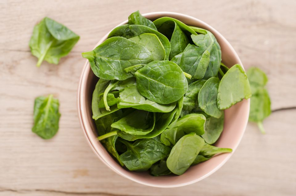 Bowl of fresh spinach leaves on wood