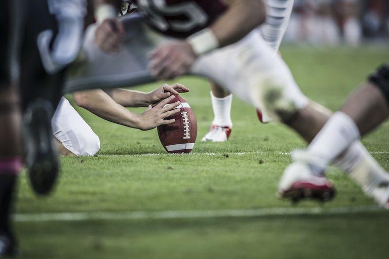 American football players readying to kick ball.
