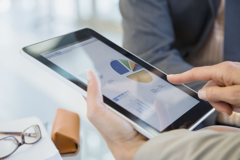 Business people reviewing financial data on digital tablet