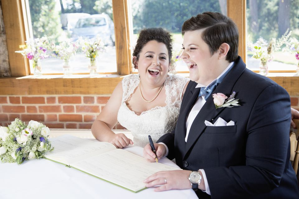 Happy lesbian couple signing the register.