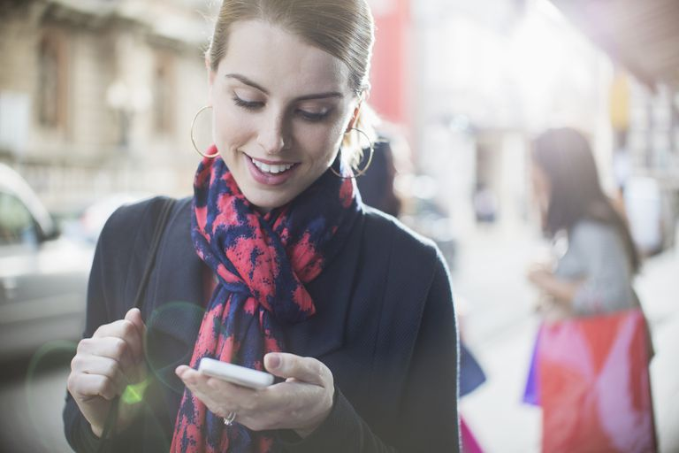 Woman looking at cell phone on sidewalk