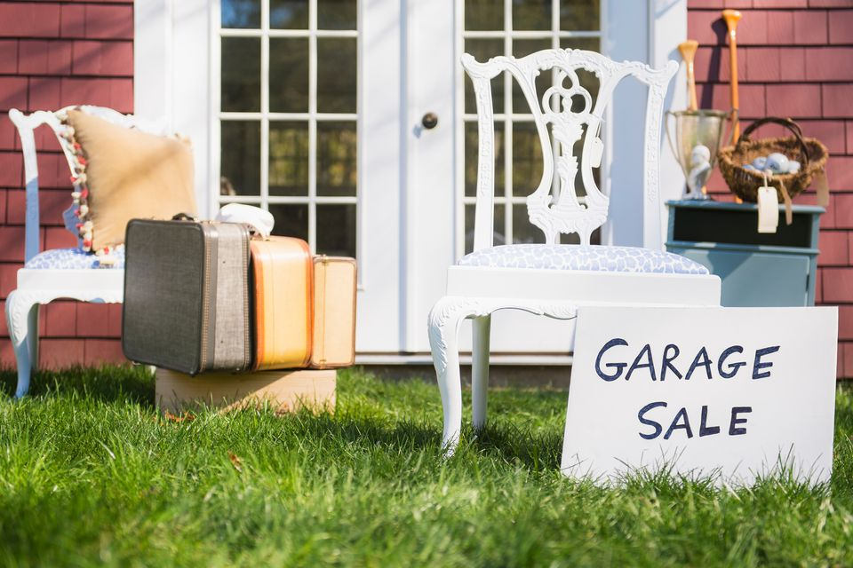 garage sale with antique chairs and vintage luggage