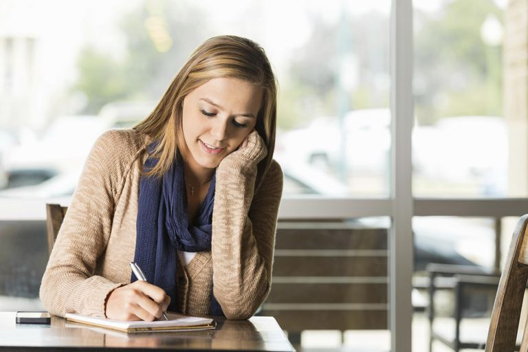 College age girl writing in journal at coffee shop