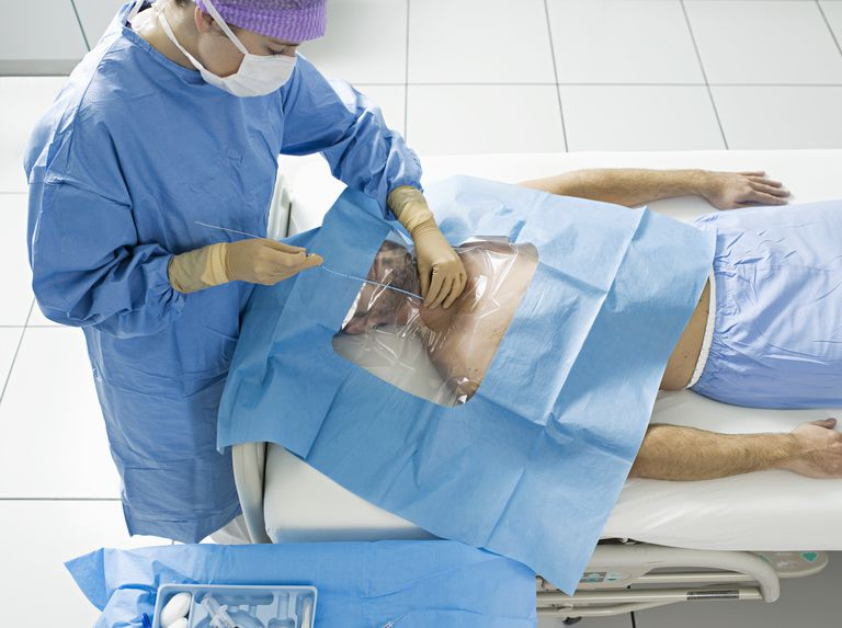 Young man receiving a non-tunneled central venous catheter.