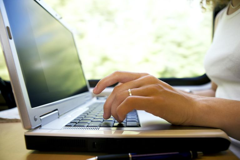 typing hands on laptop A young woman is wo...