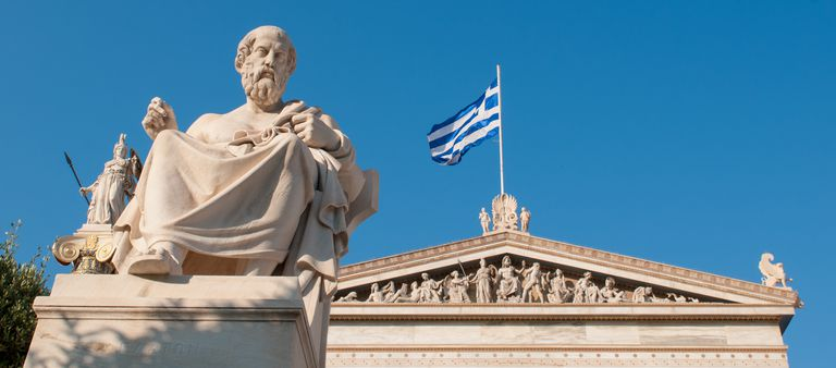 Statue of Plato in front of building with Greek flag