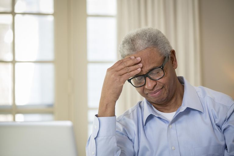Senior African American man rubbing his forehead