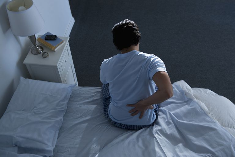 USA, New Jersey, Jersey City, Man sitting on bed