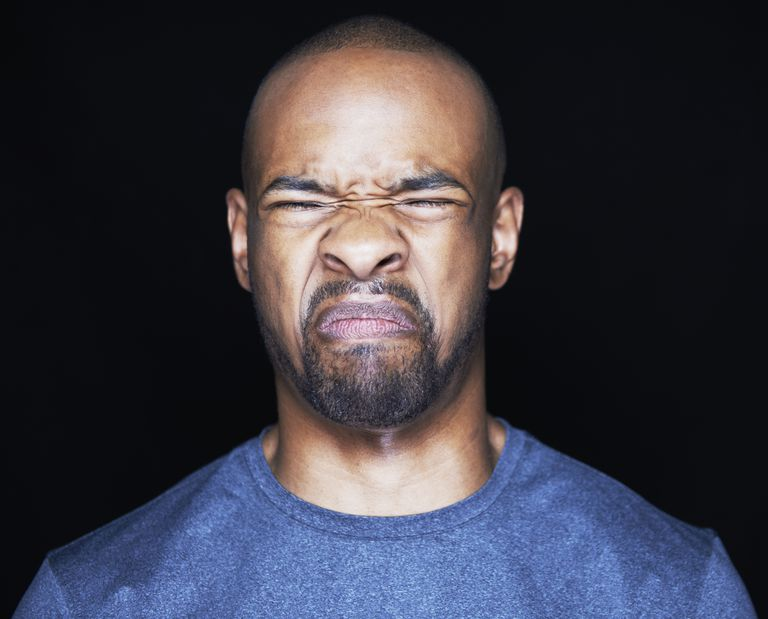 A black man facing the camera, eyes closed, looking disgusted.