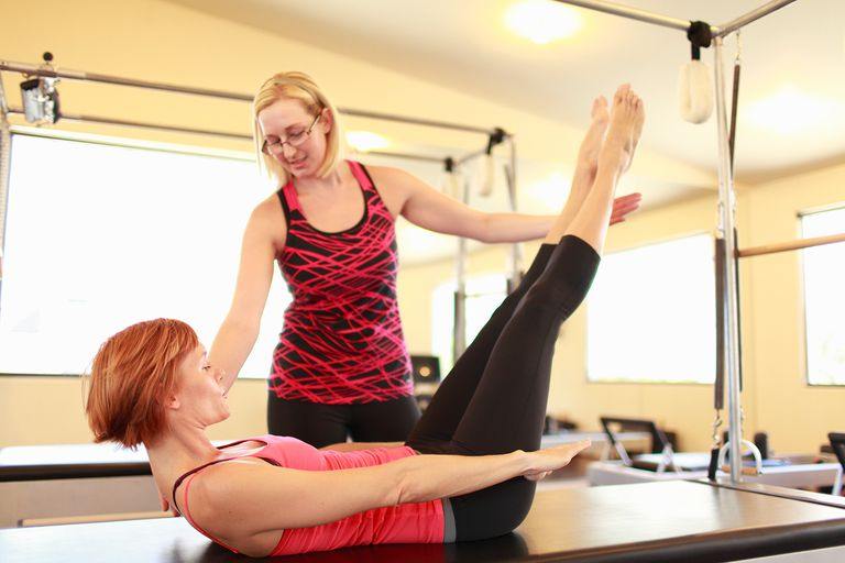 Instructor and client working in a gym on equipment designed for pilates exercise routines.