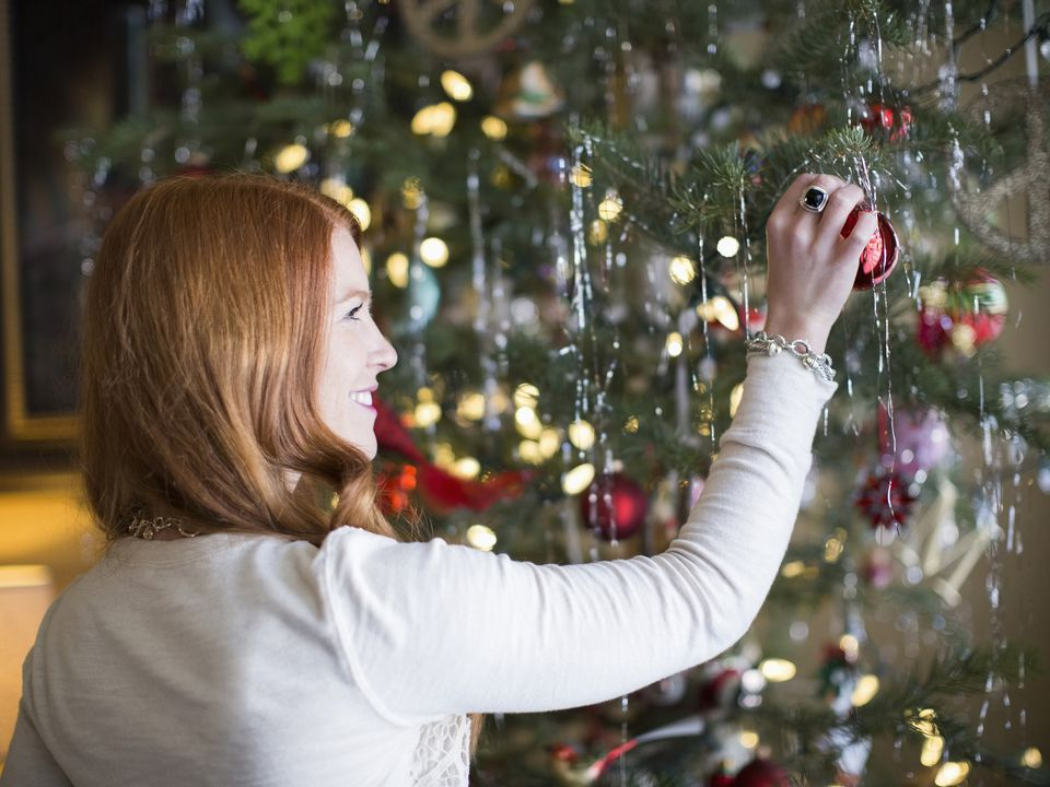 Mid adult woman decorating Christmas tree