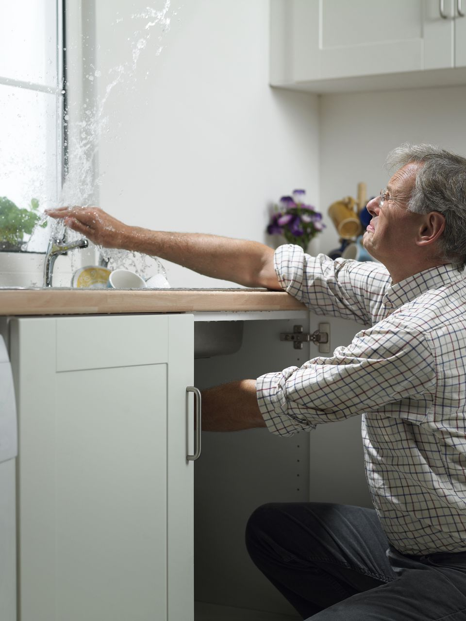 Man attempting to fix sink in kitchen
