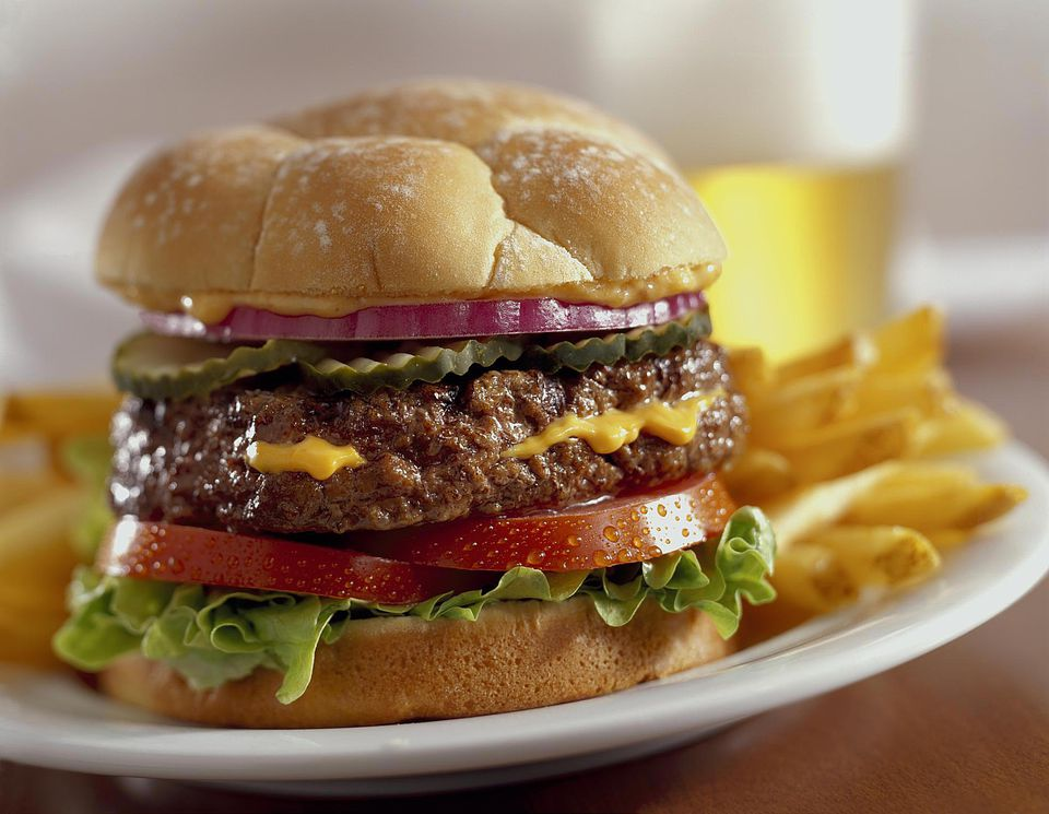 A cheese stuffed burger with french fries