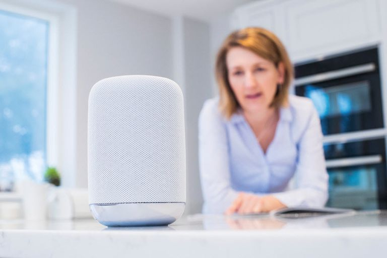 Woman blurred in background in kitchen asking Google Home for calendar informaiton