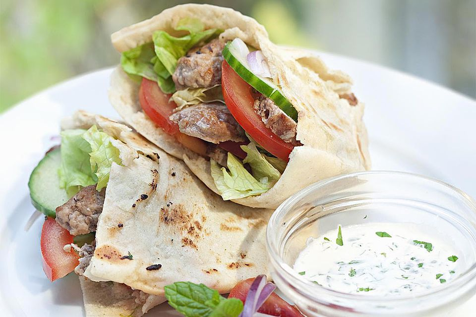 A lamb gyro with a side of tzatziki sauce