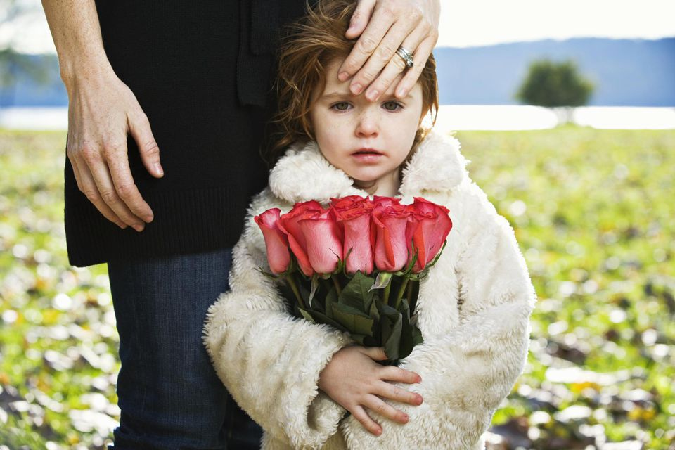 Mother and child with flowers mourn the death of a grandparent