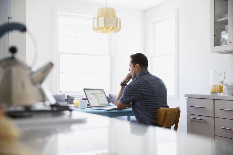 man on laptop in kitchen