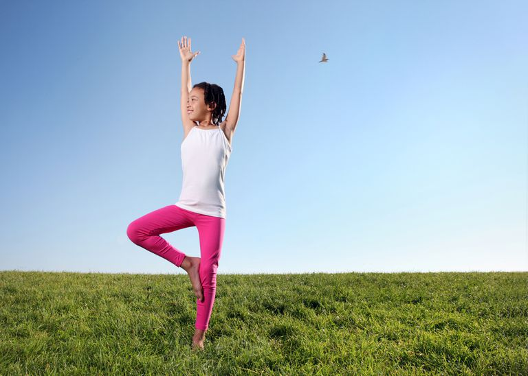 young girl doing tree pose outside