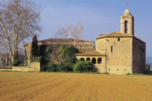 high-walled, brown stone Spanish castle with tiled roof