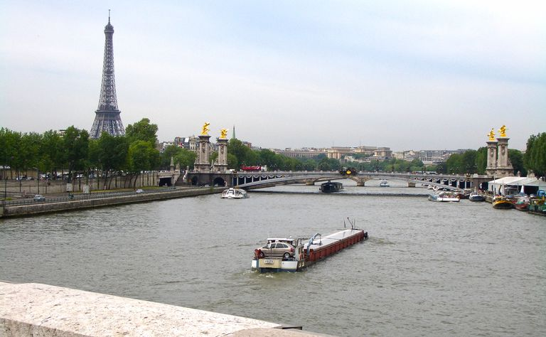 A barge travels along the River Seine in central Paris with bridges and the Eiffel Tower nearby.