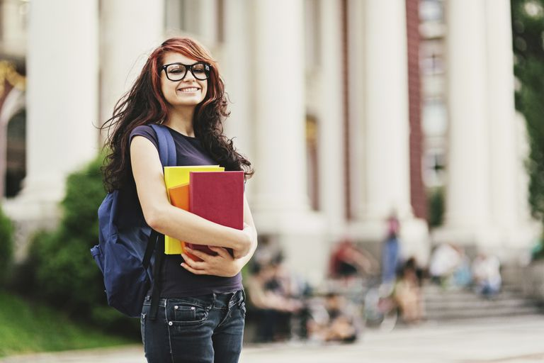 College aged woman holding books at school