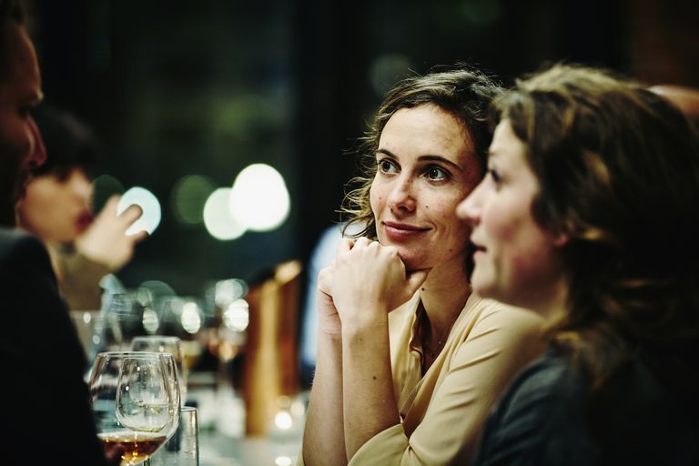 Smiling friends talking at dinner party