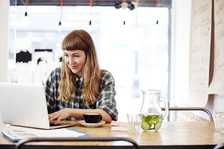Woman smiling at website on laptop