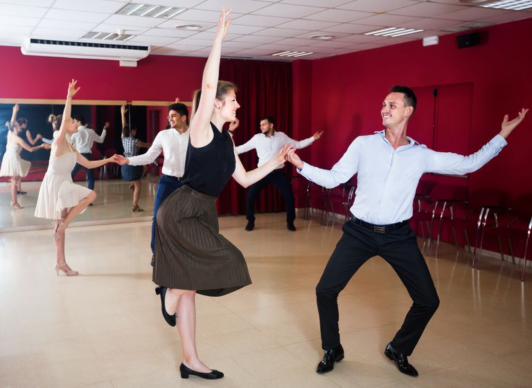 Adult people dancing lindy hop in pairs