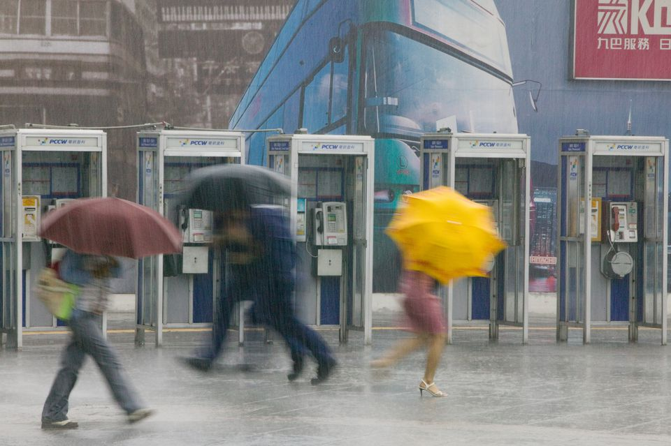 Pedestrians, payphone and a typhoon