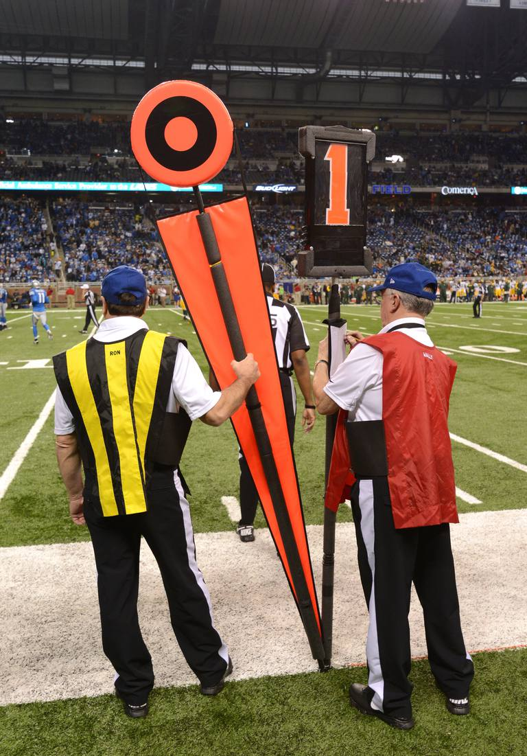 Members of the chain gang stand on the sidelines with markers during the game between the Detroit Lions and the Green Bay Packers at Ford Field on November 28, 2013