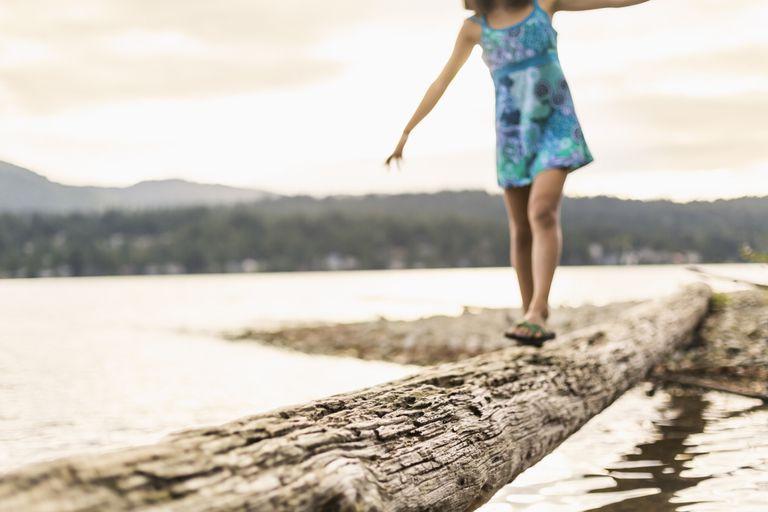 Photo of a girl balancing on a log.