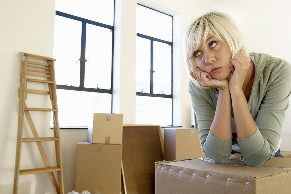 Girl looking bored with a packed moving box