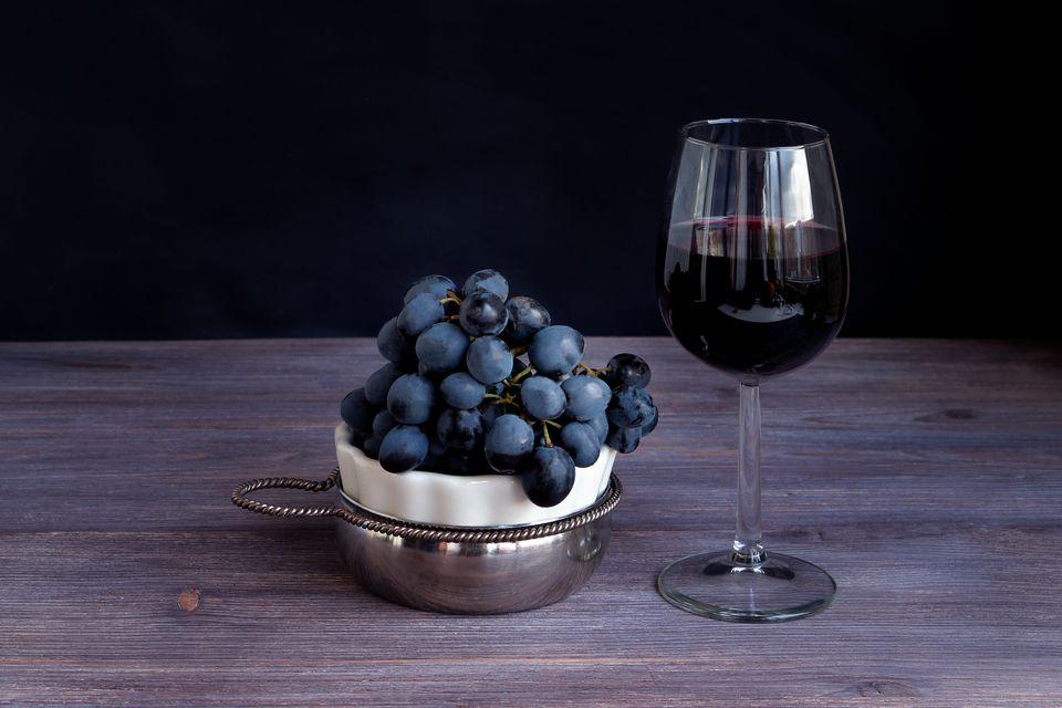 Sangiovese in wine glass, bunch of dark purple grapes