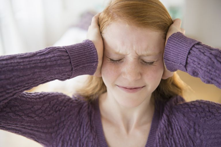 Front view of teen with hands on her head