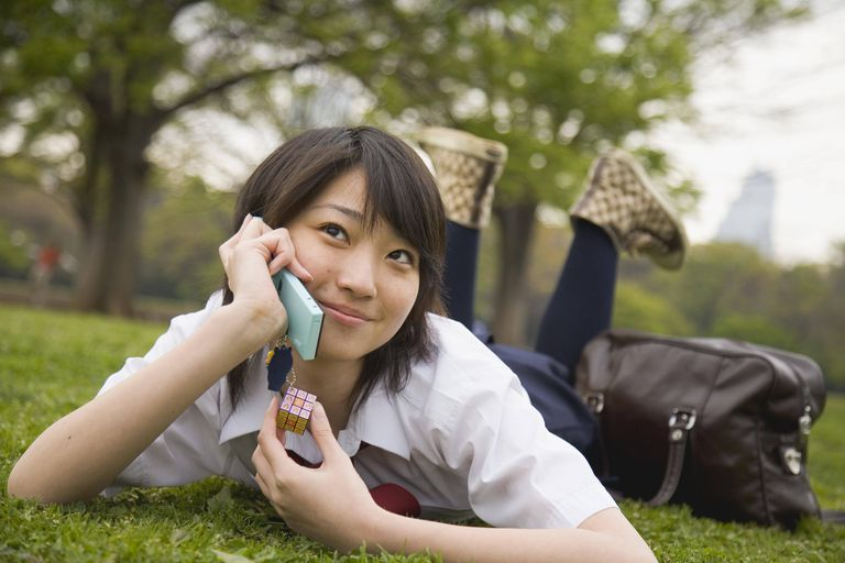 Teenage girl talking on cell phone lying on the grass