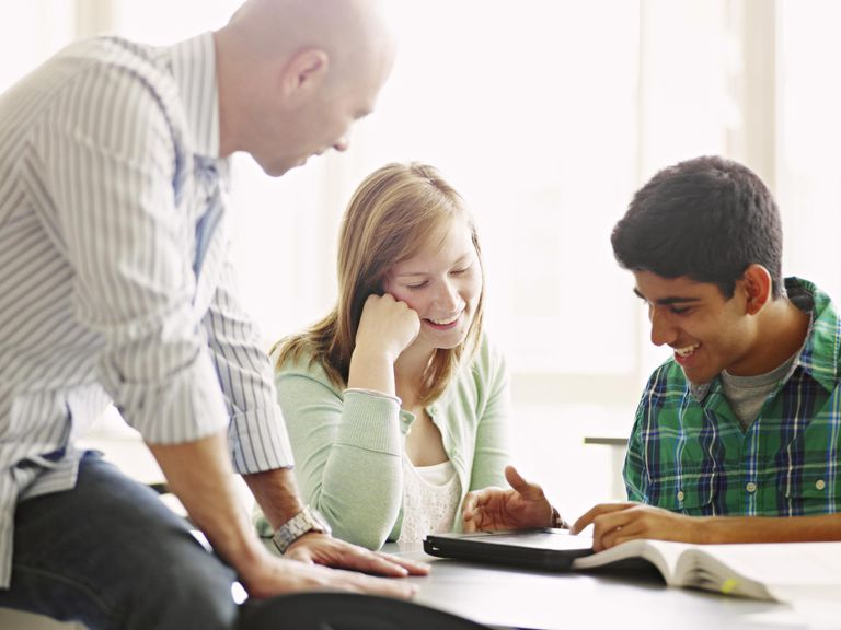 School psychologist helping students working on digital tablet