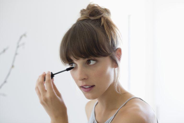 close-up of woman putting on mascara