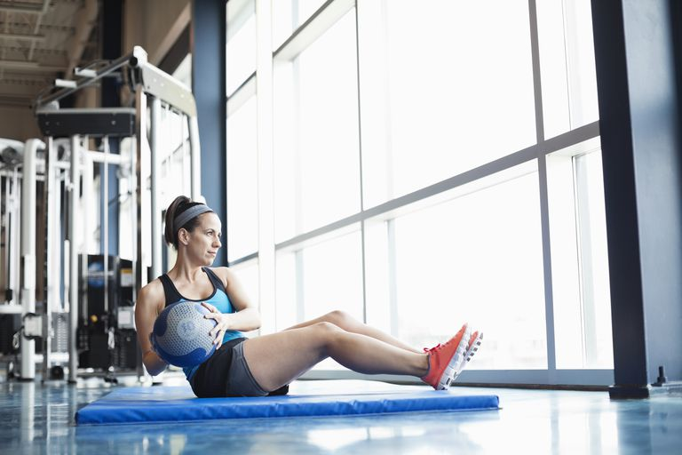 Woman exercising with medicine ball in fitness center