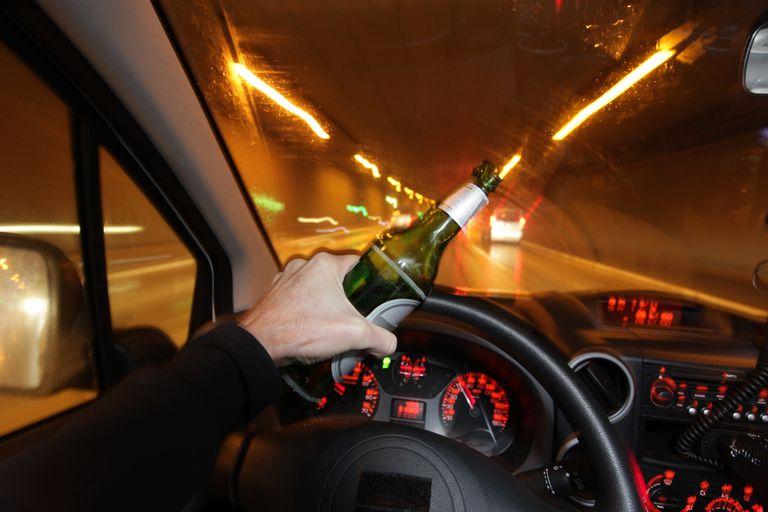 Chofer manejando con botella de cerveza en mano. Manejar ebrio puede tener consecuencias migratorias.