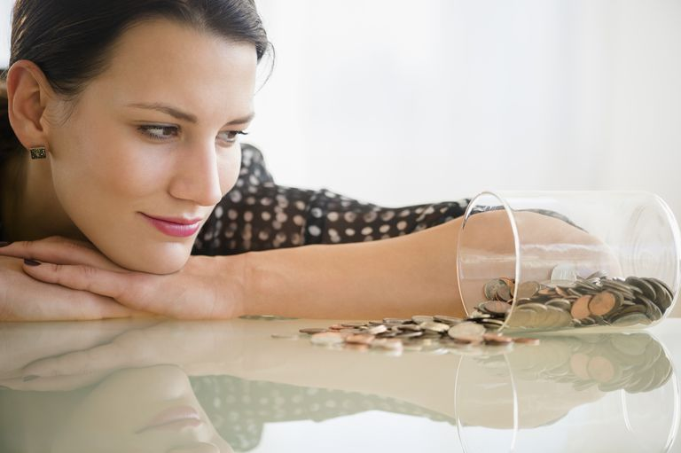 Woman looking at jar of coins