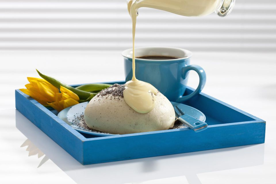 Pouring vanilla sauce on yeast dumpling beside coffee cup and tulip