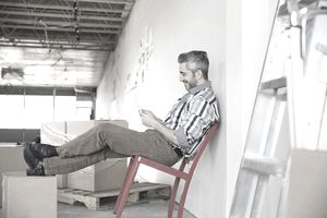 Businessman using cell phone in new office