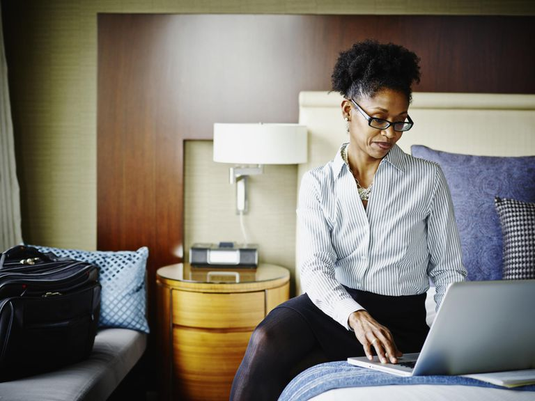 Businesswoman in hotel suite working on laptop