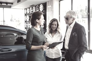 Car saleswoman selling car to couple