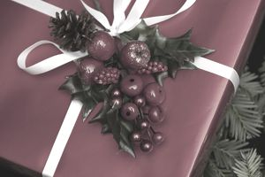 Gift box wrapped in red paper, white ribbon, and a spring of winter berries.