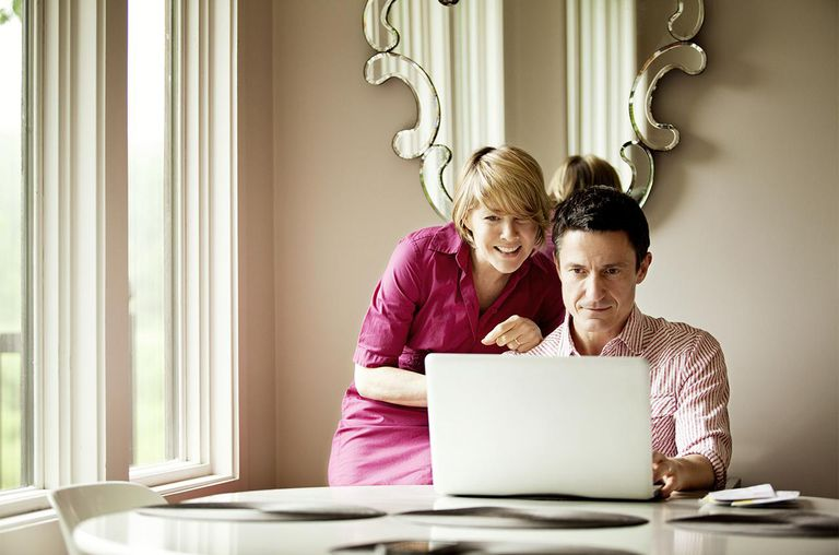 Couple Looking At Computer At Kitchen Table