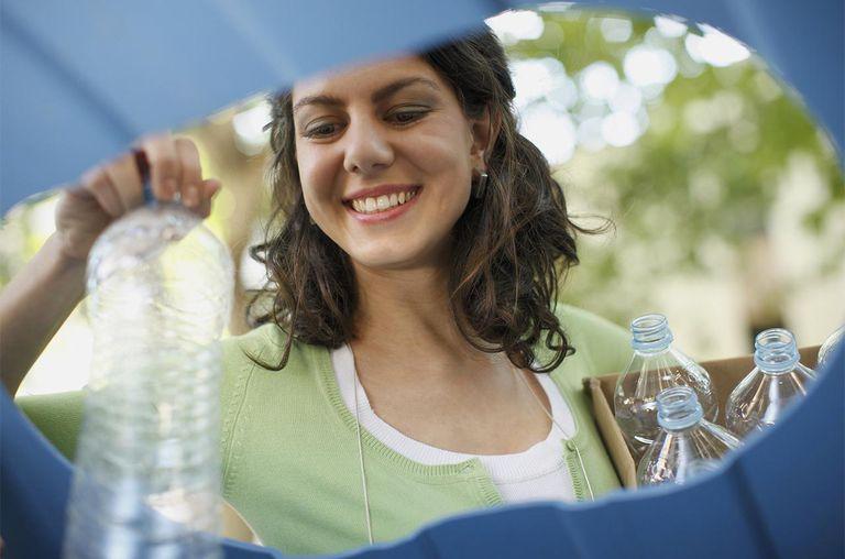 Businesswoman recycling water bottles