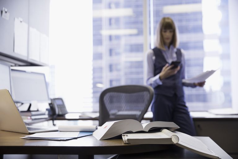 Female lawyer reviewing paperwork and texting with cell phone in office