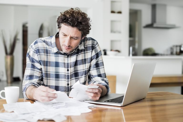man looking through receipts and bills with laptop and a cup of coffee